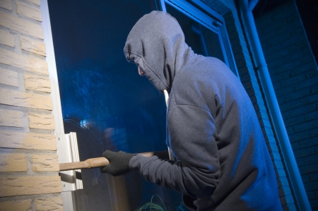 A burglar is trying to get into a house by the backdoor Standard-Bild