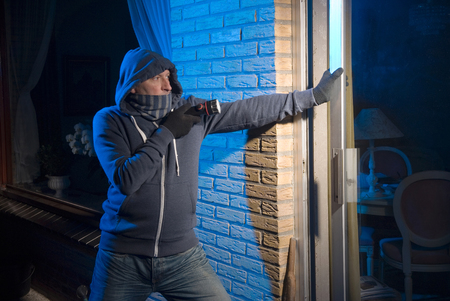 backdoor: A burglar is opening the backdoor of a house