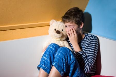 若い男の子は彼の寝室で彼のベッドで泣いています。