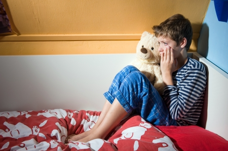 A young boy is crying on his bed in his bedroom photo