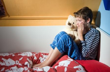 abuso sexual: Un ni�o est� llorando en su cama en su dormitorio