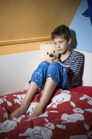molestation: A young boy is sitting sad and depressed on his bed in his bedroom