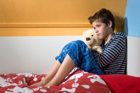 若い男の子は彼の寝室で彼のベッドに悲しんで、落ち込んでいる座っています。
