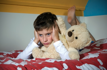 A young boy is lying sad and angry on his bed in his bedroom photo