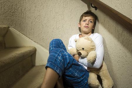abuso sexual: Un niño triste y deprimido está sentado en la esquina de una escalera
