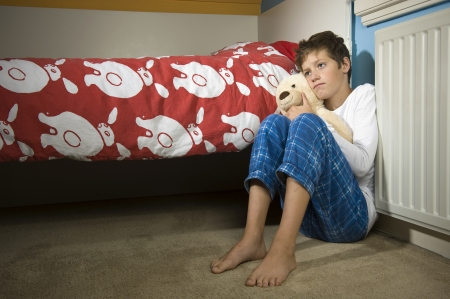 molestation: A young boy is sitting sad and depressed against his bed in his bedroom