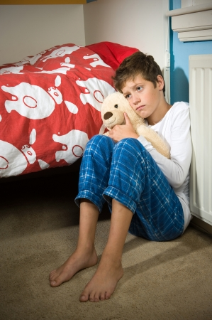 A young boy is sitting sad and depressed against his bed in his bedroom photo