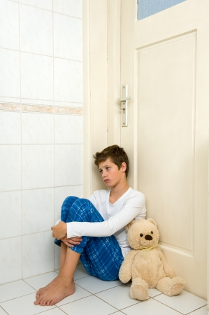 molestation: A young boy is sitting afraid and depressed in the corner of the bathroom with his bear