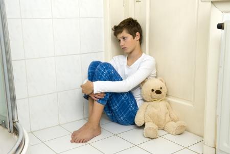 abuso sexual: Un joven está sentado miedo y depresión en la esquina del cuarto de baño con su oso
