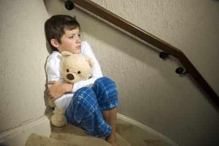 maltrato infantil: Un niño triste y deprimido está sentado en la esquina de una escalera