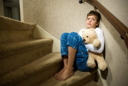 A sad and depressed boy is sitting in the corner of a staircase photo