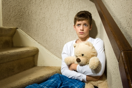 molestation: A sad and angry boy is sitting in the corner of a staircase Stock Photo