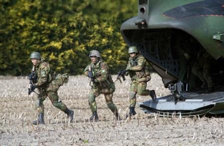 chinook: GEESTEREN, PAESI BASSI - 25 marzo soldati Mimetizzata con armi automatiche a lasciare un elicottero Chinook durante un allenamento dell'esercito olandese in una fredda giornata, 25 marzo 2013 nei Paesi Bassi Editoriali