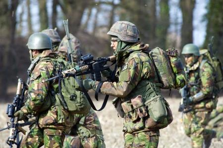 batallón: Geesteren, PAÍSES BAJOS - 25 DE MARZO Un batallón de soldados con armas automáticas durante un entrenamiento de las fuerzas especiales del ejército holandés en un día frío, 25 de marzo de 2013, de los Países Bajos Editorial