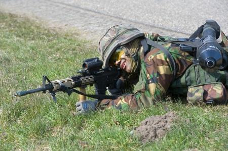 batallón: Geesteren, PAÍSES BAJOS - 25 DE MARZO Un soldado camuflado está apuntando su arma automática durante el entrenamiento de las fuerzas especiales en un día frío, 25 de marzo de 2013, de los Países Bajos Editorial