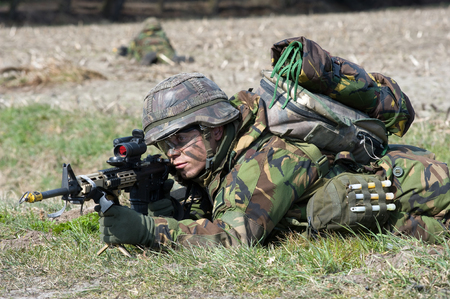 batallón: Geesteren, PAÍSES BAJOS - 25 DE MARZO Un soldado camuflado está apuntando su arma automática durante un entrenamiento en el campo abierto de las fuerzas especiales en un día frío, 25 de marzo de 2013, de los Países Bajos Editorial