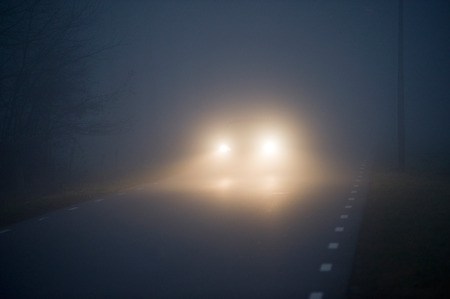 headlights: A car is slowly drivng in the mist on a december evening in the Netherlands