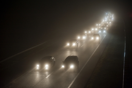 headlights: A convoy on a misty evening on a highway in december in the Netherlands