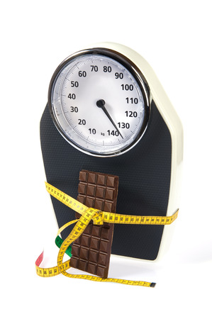 A scale with measuring tape and chocolate photo