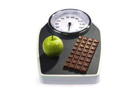 A weight scale with chocolate and an apple photo