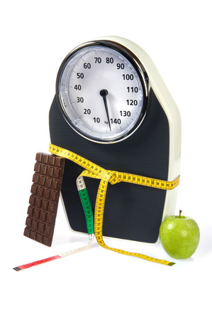 A scale with measuring tape, chocolate and an apple photo
