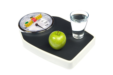 anorexia: A weight scale with measuring tape, an apple and a glass of water