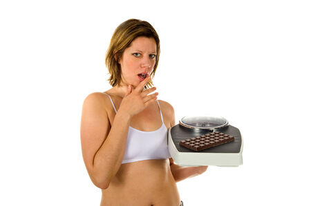 A woman wants to eat a piece of chocolate but is thinking about her figure photo