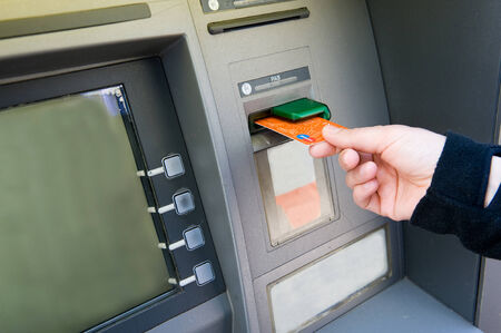 bancomat: ENSCHEDE, NETHERLANDS - APRIL 28  A woman is putting her bank card into an ATM machine to withdraw cash money, APRIL 04, 2013 in the Netherlands Editorial
