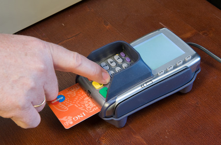 bankcard: ENSCHEDE, NETHERLANDS - MAY 15  A man is paying with his bank card using his code at a pin machine in a shop, MAY 15, 2013 in the Netherlands Editorial