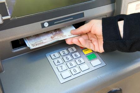 cash money: ENSCHEDE, HOLANDA - 28 de abril Una mujer est� retirando dinero en efectivo de un cajero autom�tico, 04 de abril de 2013, de los Pa�ses Bajos Editorial