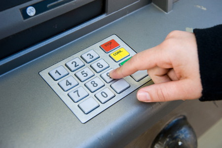 bancomat: ENSCHEDE, NETHERLANDS - APRIL 28  A woman is typing her pin code on to the keypad of an ATM machine to withdraw cash money, APRIL 04, 2013 in the Netherlands
