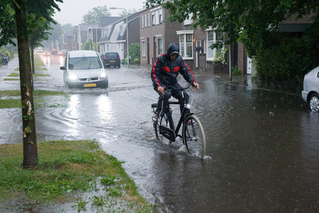 ENSCHEDE, NETHERLANDS - JUNE 06  A man on a bicycle is struggling through the high water in the streets after a downpour, JUNE 06, 2013 in the Netherlands Editorial