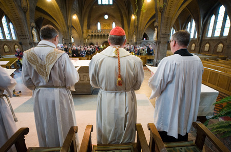 bishop: HENGELO, NETHERLANDS - JAN 15  A priest  left , a cardinal  red cap  are standing during a mass in the roman catholic