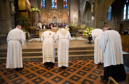 HENGELO, NEDERLAND - 9 april Een priester en een kardinaal met hun helpers buigen naar het altaar aan het einde van een mis in de rooms-katholieke