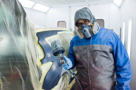 body painting: A professional car painter who is painting the body work of a car in a paint box of a garage with an airbrush
