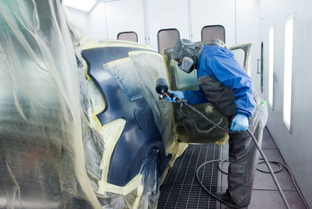 car body: A professional car painter who is painting the body work of a car in a paint box of a garage with an airbrush