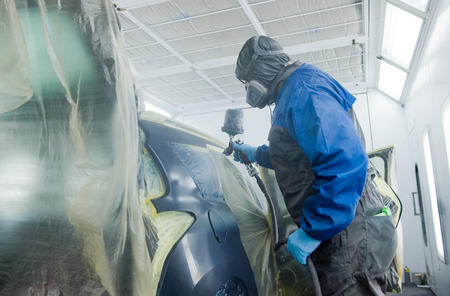 A professional car painter who is painting the body work of a car in a paint box of a garage with an airbrush