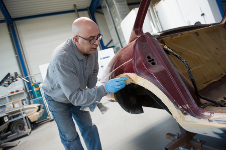 putty: A car repairman is preparing a part of a carbody for repainting in a garage Stock Photo