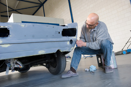 putty: A car repairman is restoring the carbody of an old timer for repainting in a garage