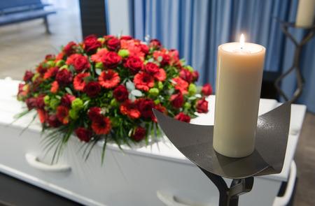 arreglo floral: Un ata�d con un arreglo de flores en una morgue y una vela encendida delante Foto de archivo
