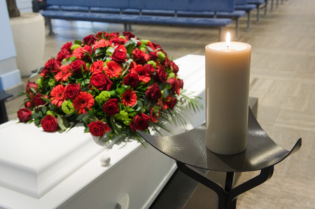 A coffin with a flower arrangement in a morgue and a burning candle in front