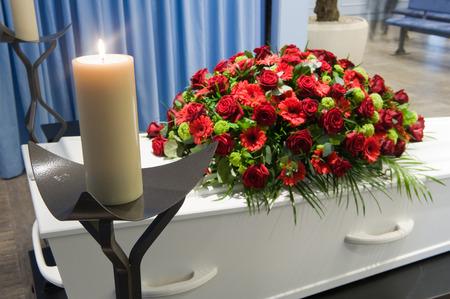 死体安置所で前に非常に熱い蝋燭のフラワーアレンジメントの棺