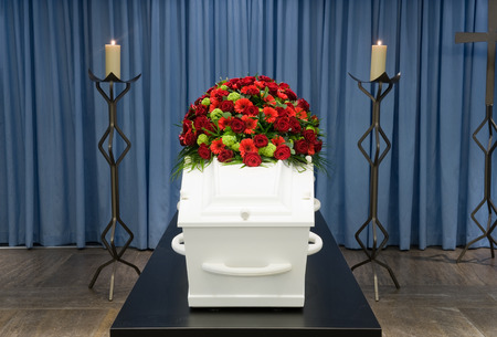 A coffin with a flower arrangement in a morgue and a burning candle in front photo