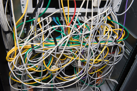 A lot of cables for internet on the back of a big computer