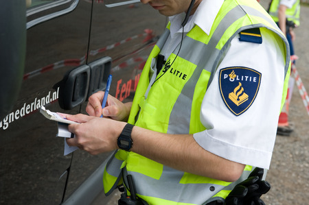 HAAKSBERGEN, NETHERLANDS - JUNE 09  A policeman is checking the driving license of a car driver during a massive traffic control, june 09, 2011 in the Netherlands