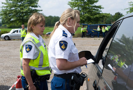 policewomen: HAAKSBERGEN, NETHERLANDS - JUNE 09  Two policewomen are checking the papers of a car driver during a massive car control, june 09, 2011 in the Netherlands Editorial