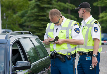 HAAKSBERGEN, NETHERLANDS - JUNE 09  A policeman is writing a ticket for a car driver who was speeding, june 09, 2011 in the Netherlands