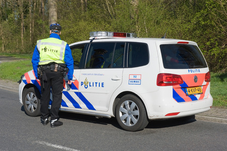 ENSCHEDE, NETHERLANDS - MARCH 25  A policeman is taking to a colleague in a police car during a surveillance on the street, march 25, 2014 in the Netherlands