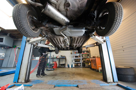 servicing: A mechanic is working on the wheel of a car who is lifted up in a repair service station