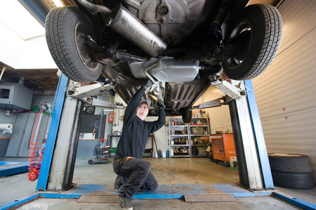 A mechanic is checking the exhaust of a car who is lifted up in a repair service station  版權商用圖片
